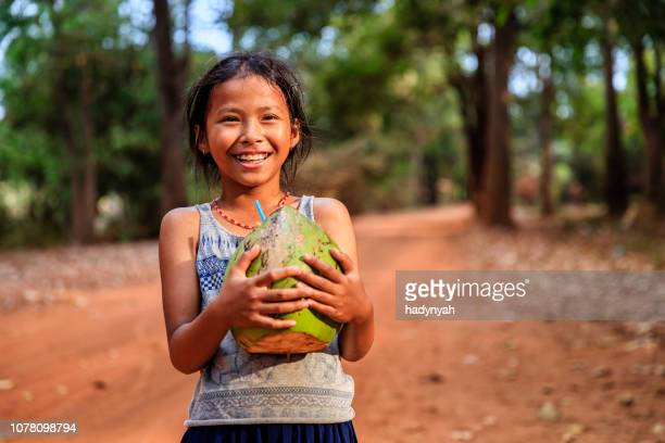 happy cambodian girl holding fresh coconut, cambodia - coconut water stock pictures, royalty-free photos & images
