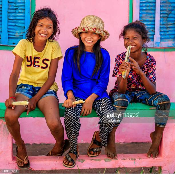 Happy Cambodian girls eating a sugar cane, Cambodia