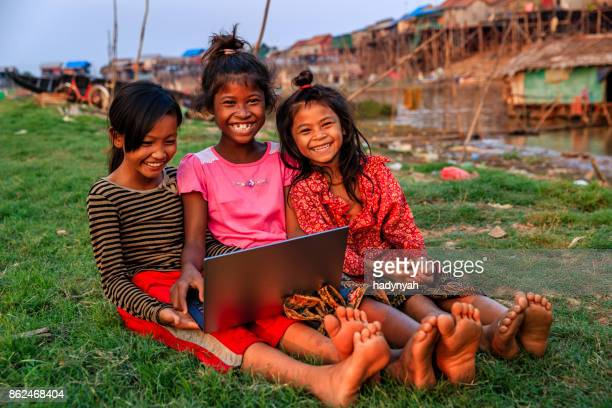 Happy Cambodian girls using laptop in village, Cambodia