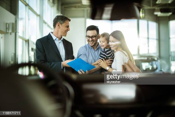 happy car salesperson making plans with young family in a showroom. - car salesperson stock pictures, royalty-free photos & images