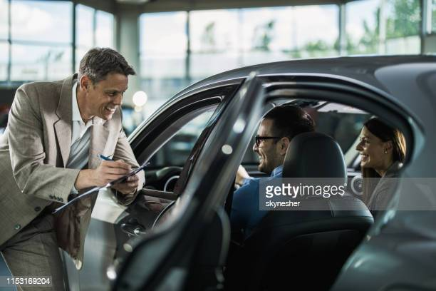 happy car salesperson talking to young couple in a showroom. - test drive stock pictures, royalty-free photos & images