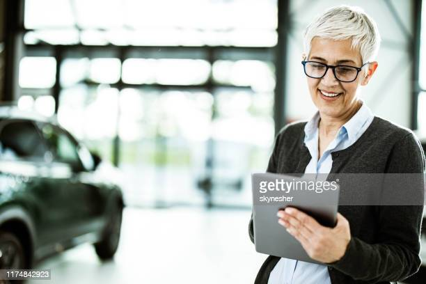 happy car salesperson using digital tablet in a showroom. - car dealership stock pictures, royalty-free photos & images
