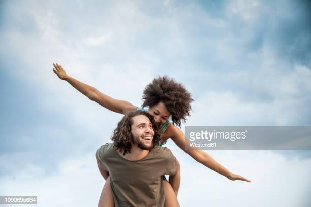 happy carefree couple outdoors - portare a cavalluccio foto e immagini stock