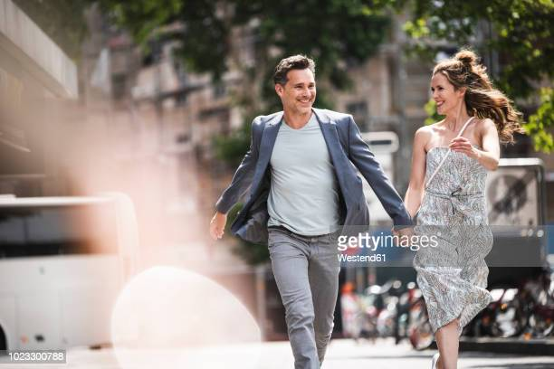 happy carefree couple running in the city - leichter stock-fotos und bilder