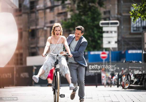 happy carefree couple with bicycle in the city - schieben stock-fotos und bilder