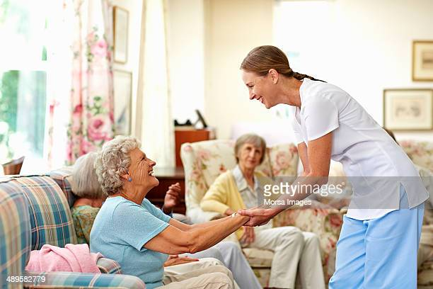 Happy caretaker assisting senior woman
