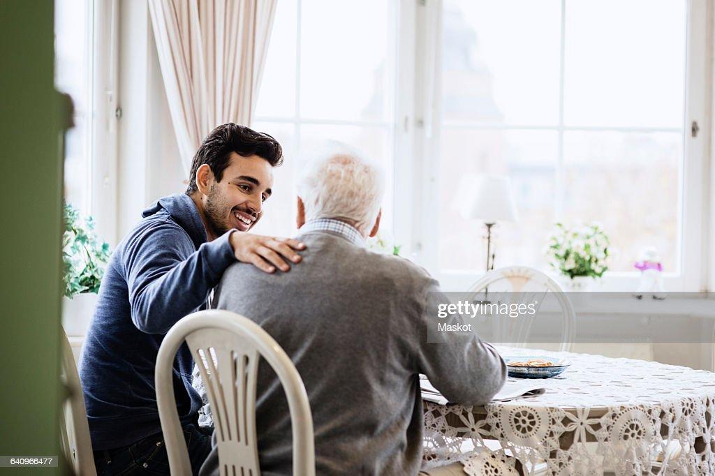 Happy caretaker communicating to senior man in nursing home : Stock Photo