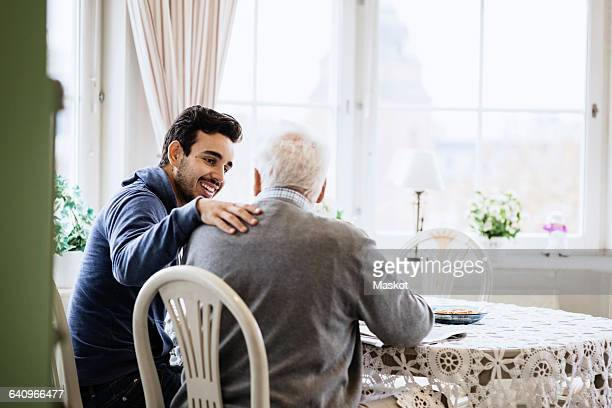 Happy caretaker communicating to senior man in nursing home