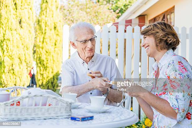 Happy caretaker offering biscuits to senior man