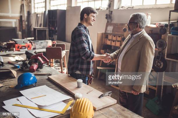 Happy carpenter shaking hands with a customer in wood factory.