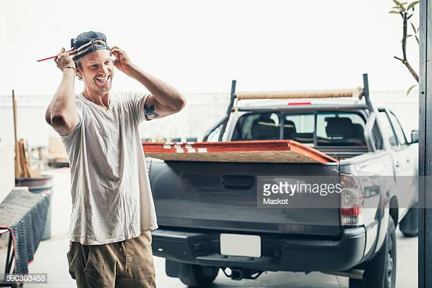 Happy carpenter standing by pick-up truck outside workshop