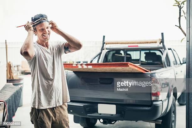 happy carpenter standing by pick-up truck outside workshop - designer einrichtung stock-fotos und bilder