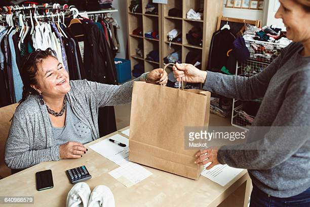 happy cashier giving shopping bag to customer in clothing store - disability collection stock pictures, royalty-free photos & images
