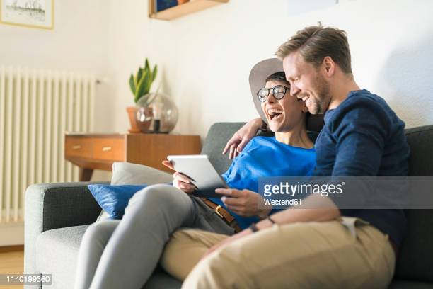 happy casual couple relaxing on couch using tablet and laughing - it movie stock pictures, royalty-free photos & images