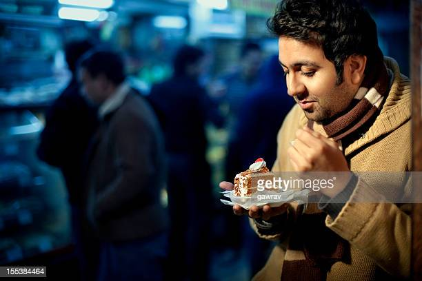 Happy casual young man eating cake near a bakery