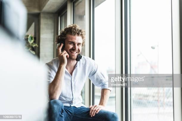happy casual young man listening to music with headphones at the window - in den zwanzigern stock-fotos und bilder