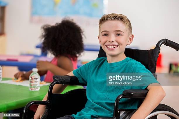 Happy Caucasian boy sitting in a wheelchair during school