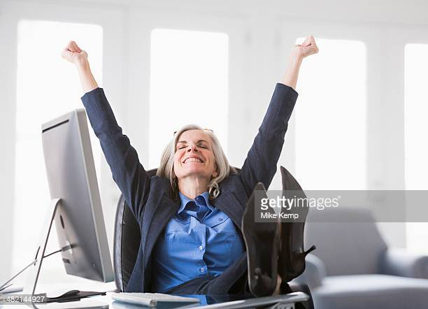 Happy Caucasian businesswoman with feet up on desk
