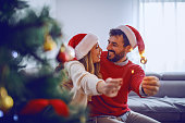 happy caucasian couple with santa hats