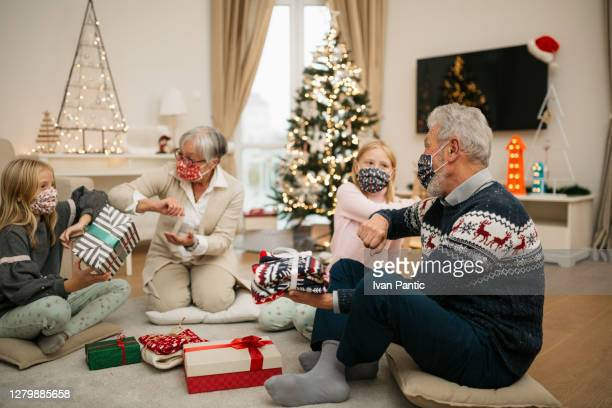happy caucasian family enjoying the winter holidays at home, elbow bump greetings - coronavirus winter stock pictures, royalty-free photos & images