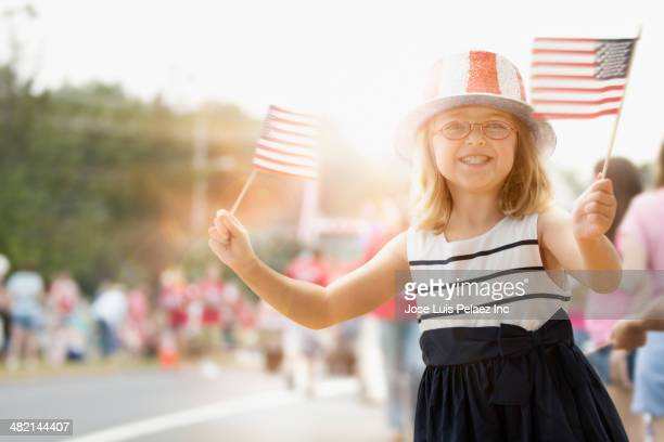 happy caucasian girl waving american flags at parade - parade stock pictures, royalty-free photos & images