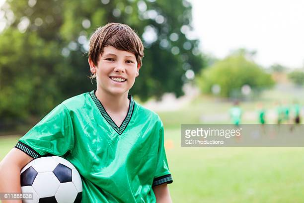 Happy Caucasian soccer player with ball