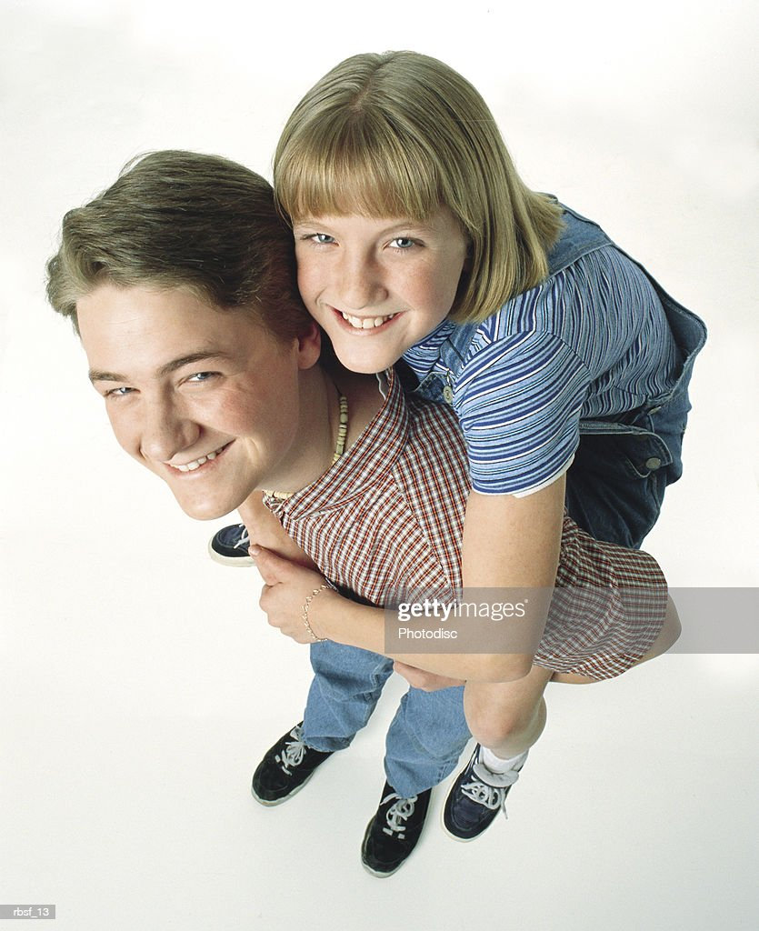 happy caucasian teenage boy gives his teen sister a piggy-back ride : Foto de stock