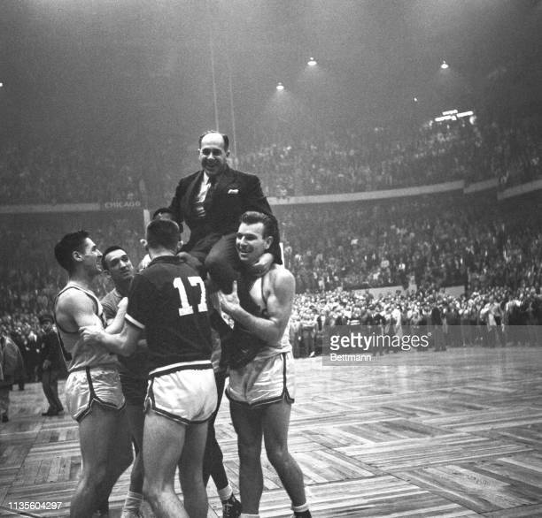 Happy Celtics players hoist their coach Red Auerbach to their shoulders after downing the Syracuse Nationals 8380 making it three straight over the...