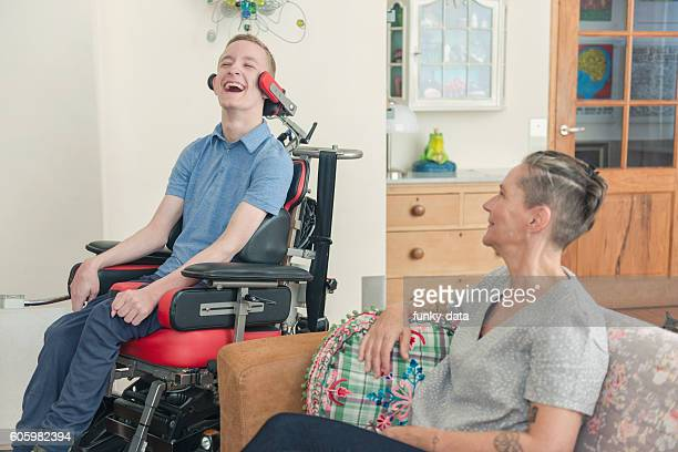 happy cerebral palsy patient with his mom - paraplegic stock photos and pictures