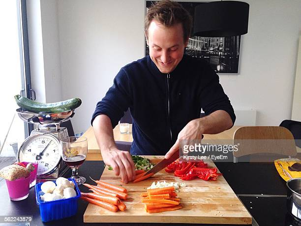 happy chef chopping vegetables on cutting board - 根菜 ストックフォトと画像