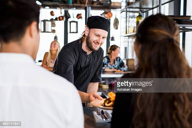 Happy chef serving dish to customers at sky bar restaurant