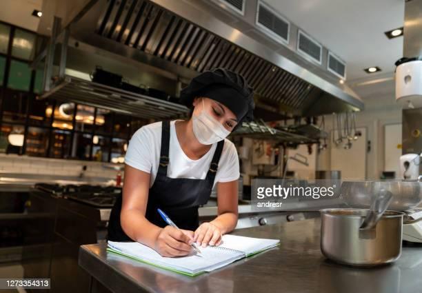 chef feliz trabalhando em um restaurante usando uma máscara facial na cozinha - instruções - fotografias e filmes do acervo