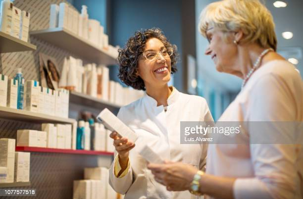 happy chemist assisting senior customer at drugstore - cream colored stock pictures, royalty-free photos & images