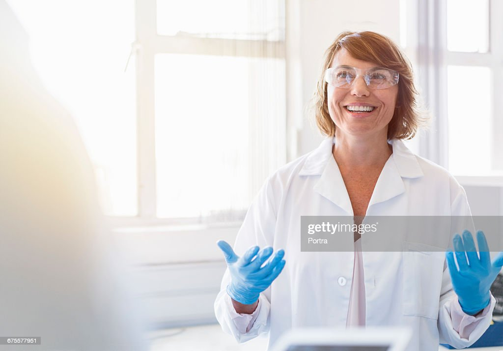 Happy chemist gesturing and talking in laboratory : Stock-Foto