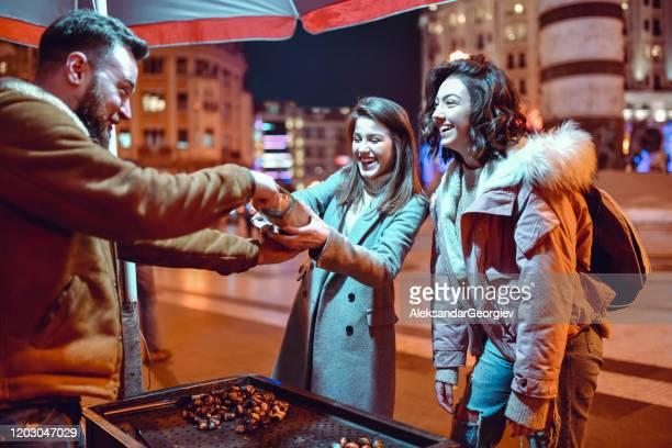 happy chestnut street baker giving females few bonus nuts - banca de mercado imagens e fotografias de stock