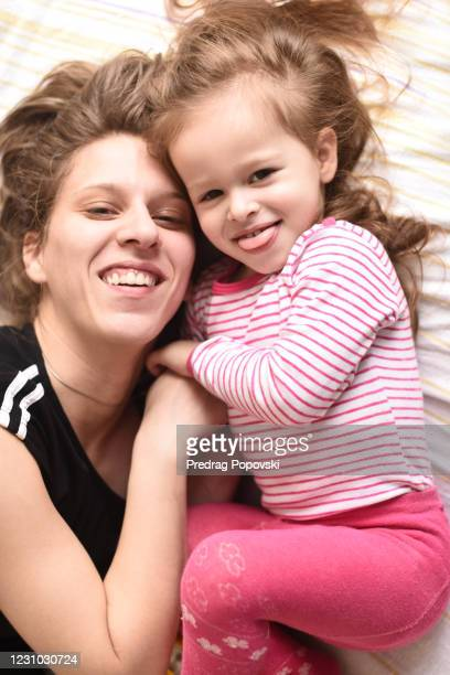 happy child and mom having fun on bed - kumanovo stock pictures, royalty-free photos & images