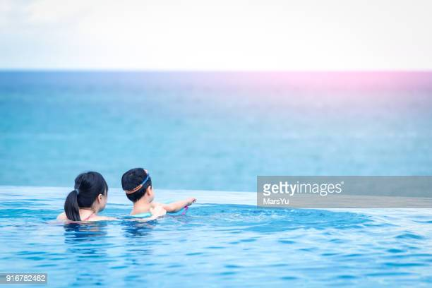 Happy child and mother in swimming pool