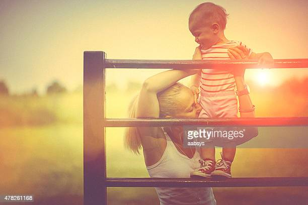 Happy child climbing supported by mother on the playground
