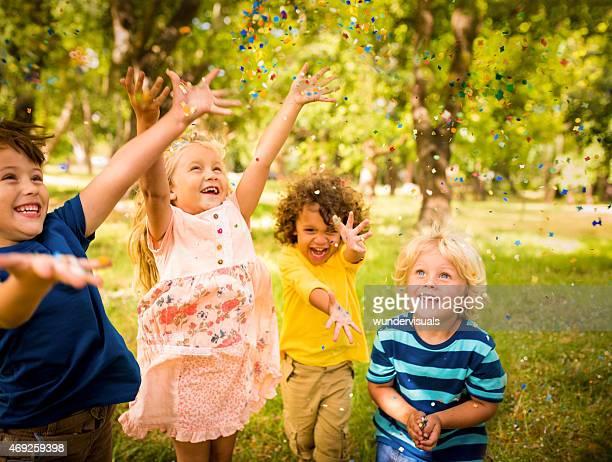 Heureux enfant amis s'amusant avec des confettis dans le parc