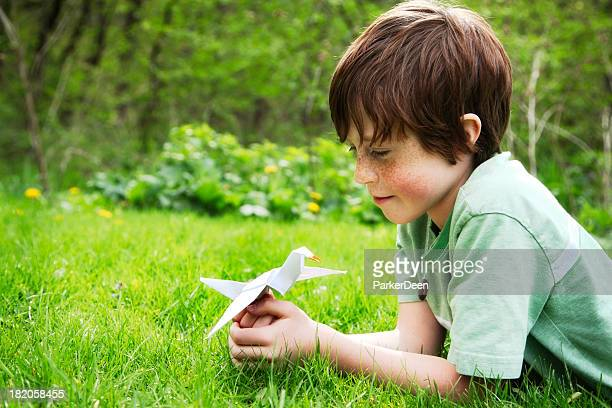 Happy Child Holding a Origami Peace Crane Outside in Nature