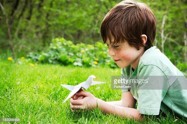 bambino felice con una gru origami pace in natura all'aperto - origami foto e immagini stock