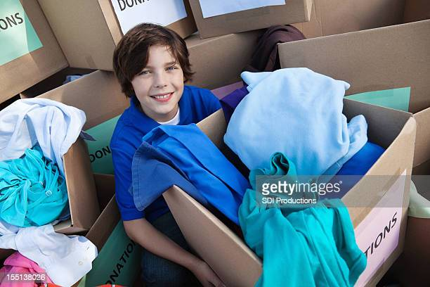 Happy child holding donation boxes at donations center