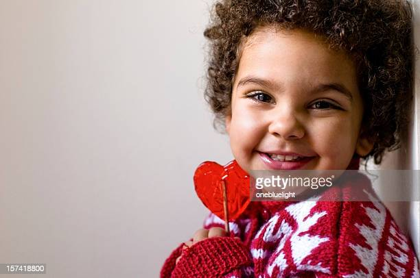 Happy Child Holding hermético su corazón forma piruleta