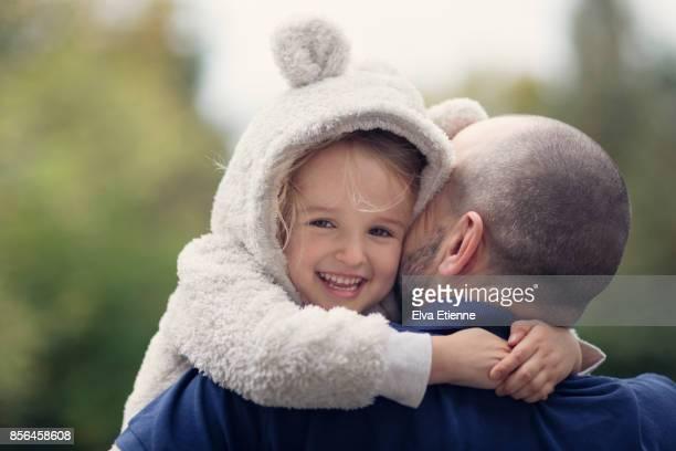 happy child in hooded bear costume, hugging father - kopfbedeckung stock-fotos und bilder