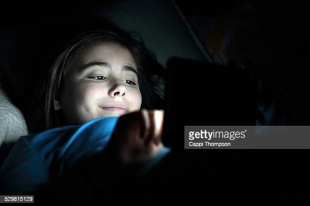 Happy child in the dark with tablet