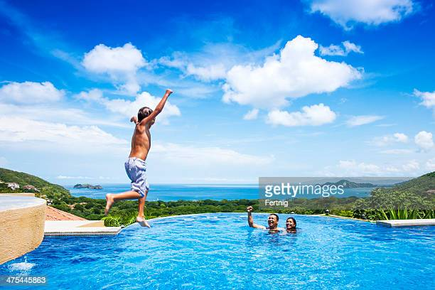 Happy child jumping into a pool in Costa Rica