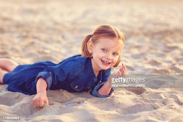 Happy child laying in the sand