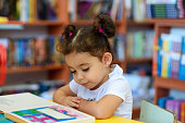 Happy child little girl reading a book.