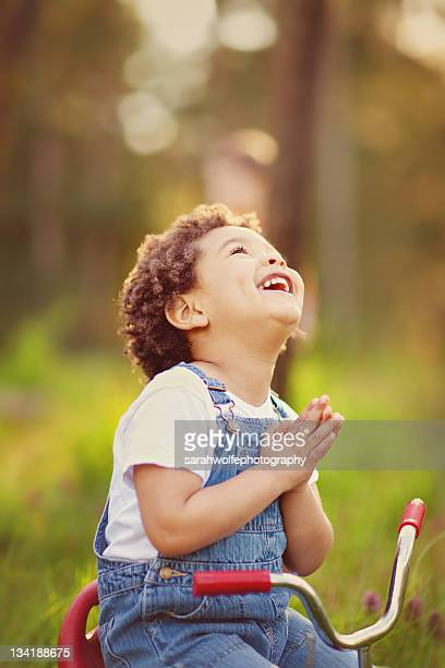 Happy child looking up with hands in praying pose