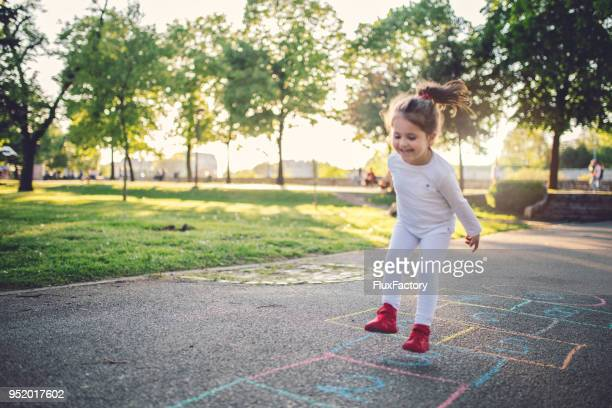 happy child on a playground - hopscotch stock pictures, royalty-free photos & images